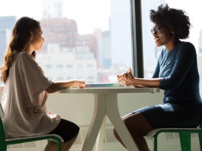 two women speaking across a table